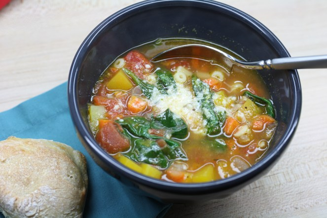 Charcoal bowl of vegetable heavy minestrone soup with a spoon and a rustic dinner roll on a teal napkin