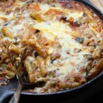 Cast Iron pan filled with cheesy Italian baked ziti, eggplant, sausage and olives. A baguette is in the background.