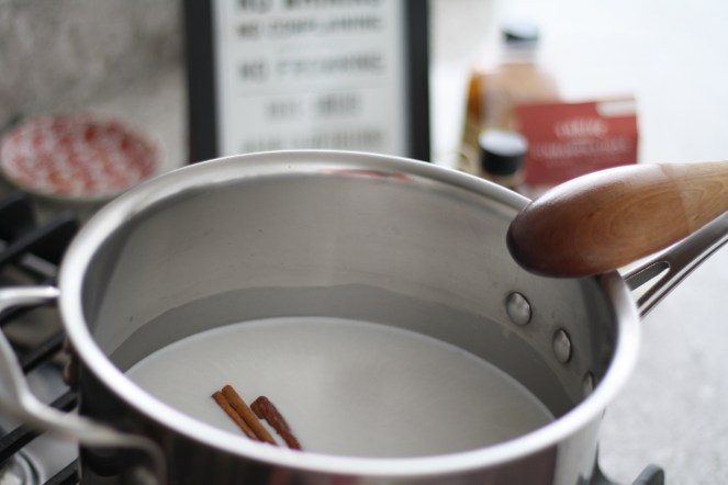 Stainless steel pot on stovetop with milk and cinnamon sticks