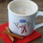 Light blue snowman mug filled with vanilla almond steamer on top of a red napkin with cinnamon sticks