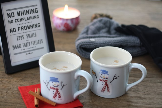 """Two light blue snowman mugs filled with vanilla almond steamer on top of a red napkin with cinnamon sticks. Hat, gloves and a pink flowered candle in the background on wooden table, and a framed sign that reads, """"No Whining, No Complaining, Absolutely No Frowning. Only Hugs, Smiles and Warm Fuzzy Feelings Are Allowed. thank you."""""""