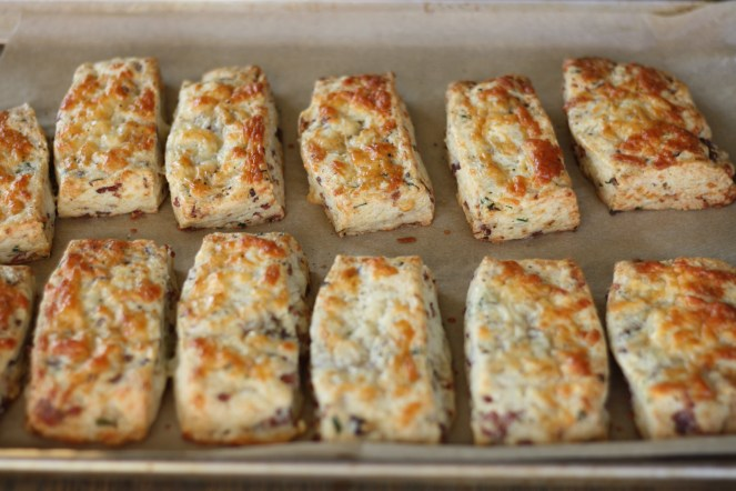 Baking sheet with 12 baked scones on top of parchment paper and baking sheet.