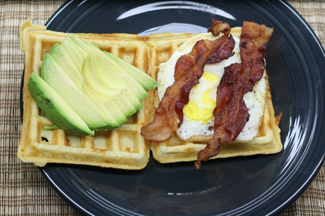 Two waffles are side by side on a charcoal colored plate. On the left waffle is half of an avocado, sliced. On the right waffle is a fried egg with two slices of bacon on top. The plate is on a brown woven placemat.