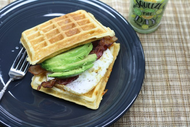 """Two waffles with a fried egg, two bacon slices and sliced avocado sandwiched in the middle. All on a charcoal colored plate on a brown woven placemat. A clear glass that says, """"Squeeze the Day"""" is filled with a green smoothie and at the upper right side of the plate on the placemat."""