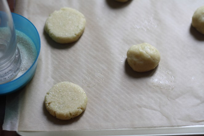 Sugar cookies on parchment-lined baking sheet. 2 are shown flattened and two are still in balls. A blue bowl is to the left, filled with sugar and a drinking glass for flattening.