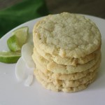 Stack of six cookies on top of a white cake stand placed on a wooden table. Coconut shavings and lime wedges are to the left of the cookies, and a green napkin is under the cake stand in the upper left corner.