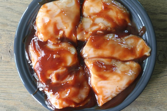 Charcoal plate with raw chicken breasts marinating in barbecue sauce. Plate is on top of a rustic wooden table.