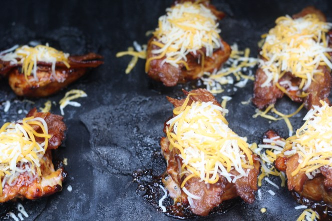 Six chicken breasts on the grill with bacon and shredded cheese on top of each.