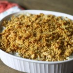 White Corningware dish filled with buttery cracker-crusted poppyseed chicken casserole on top of a wooden table with a red, white and turquoise potholder underneath
