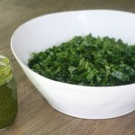 Mason jar of cilantro dressing and large white bowl filled with massaged kale on top of a wooden table