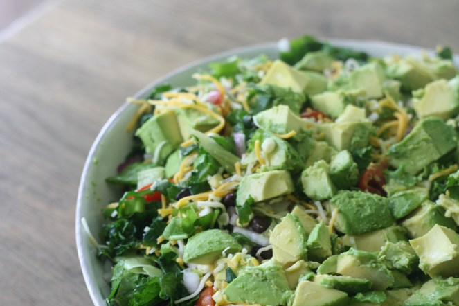 White bowl overflowing with the kale taco salad and a generous amount of avocados.