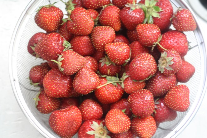 Metal colander filled with fresh strawberries