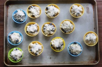 Uncooked blueberry muffins in silicone muffin cups on a metal baking sheet