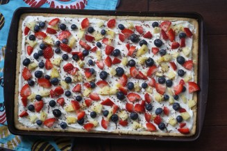 jelly roll pan filled with finished fruit pizza, loaded with strawberries, blueberries and pineapple
