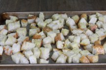Toasted bread cubes on baking sheet for panzanella