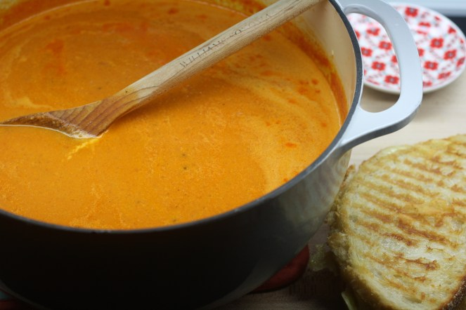 Gray pot of tomato soup with a wooden spoon resting in the soup. A grilled cheese sandwich is to the bottom right of the pot.