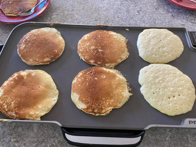 Six pancakes cooking on electric griddle