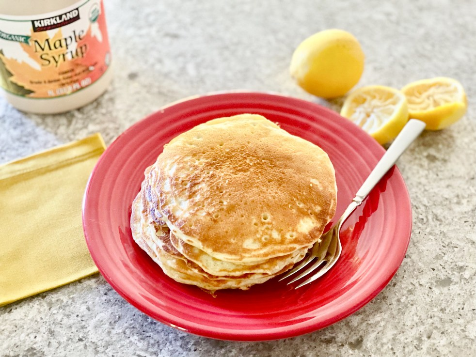 Stack of pancakes on a plate with lemons in the background