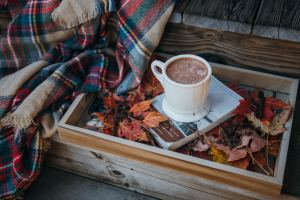 A cup of coffee standing on a book, resting in a box full of leaves.