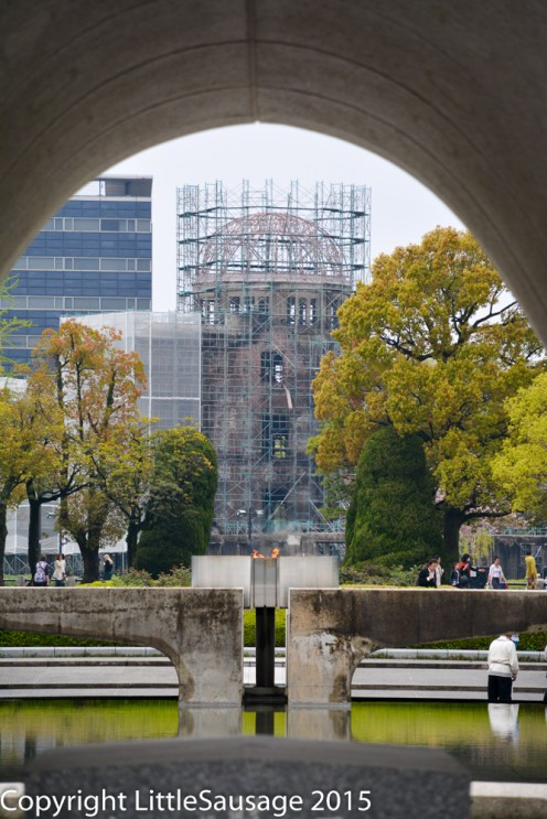 Close up of the Peace Flame through the arch of the Peace Monument and the a-bomb dome in the distance.