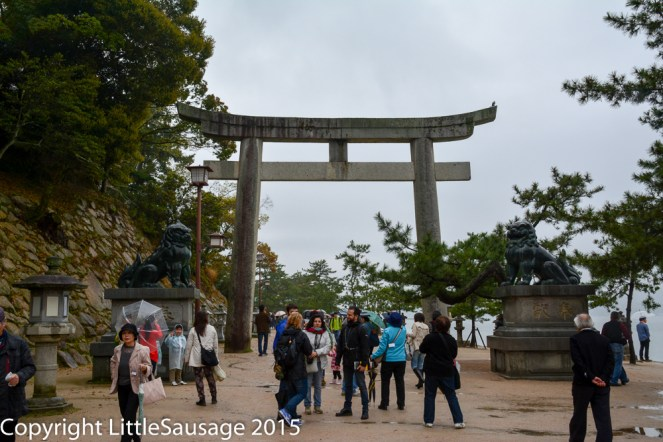 A stone torii gate on the path along the shore.