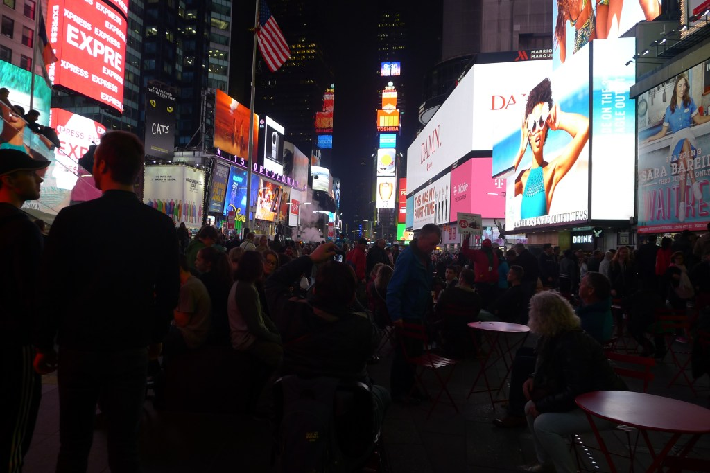 Times Square with a row of buildings and a huge crowd: Food in New York post