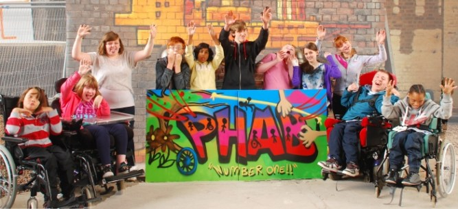 Disabled children holding the new logo of Birmingham PHAB Camps which they created together. One child is the author of the post