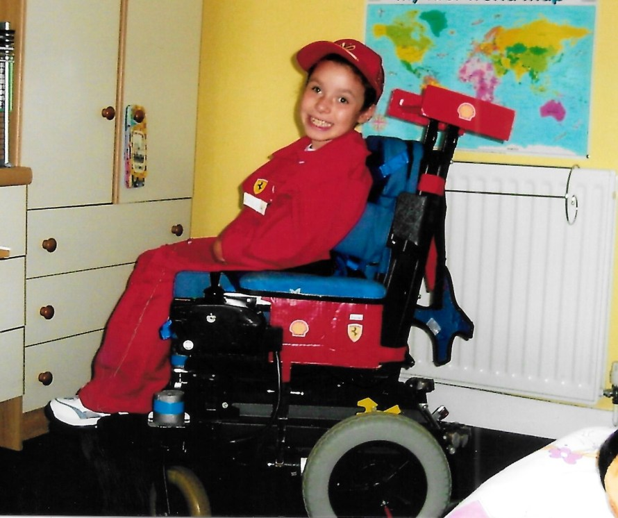 Emma at age 9 in her wheelchair, red overalls and Ferrari stickers.
