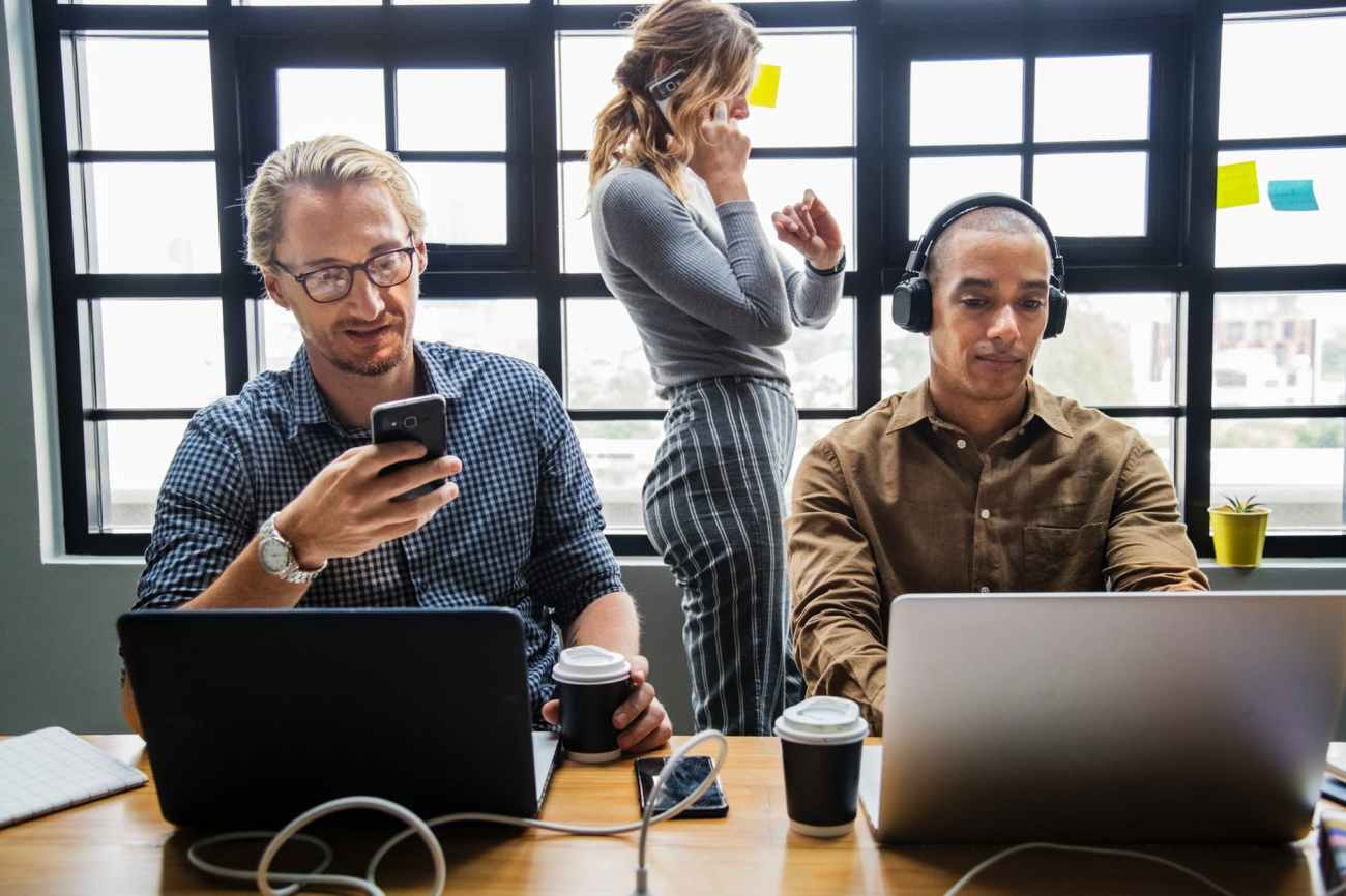 standing woman beside two men in front of laptop computer