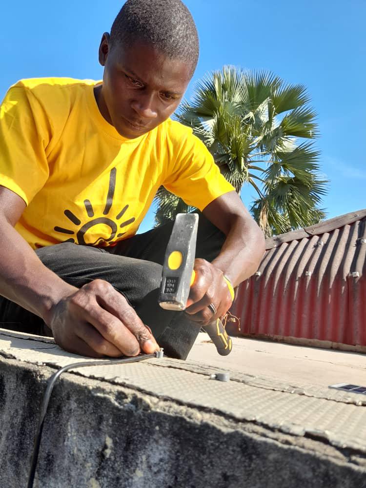 A man wearing a Little Sun shirt doing construction work