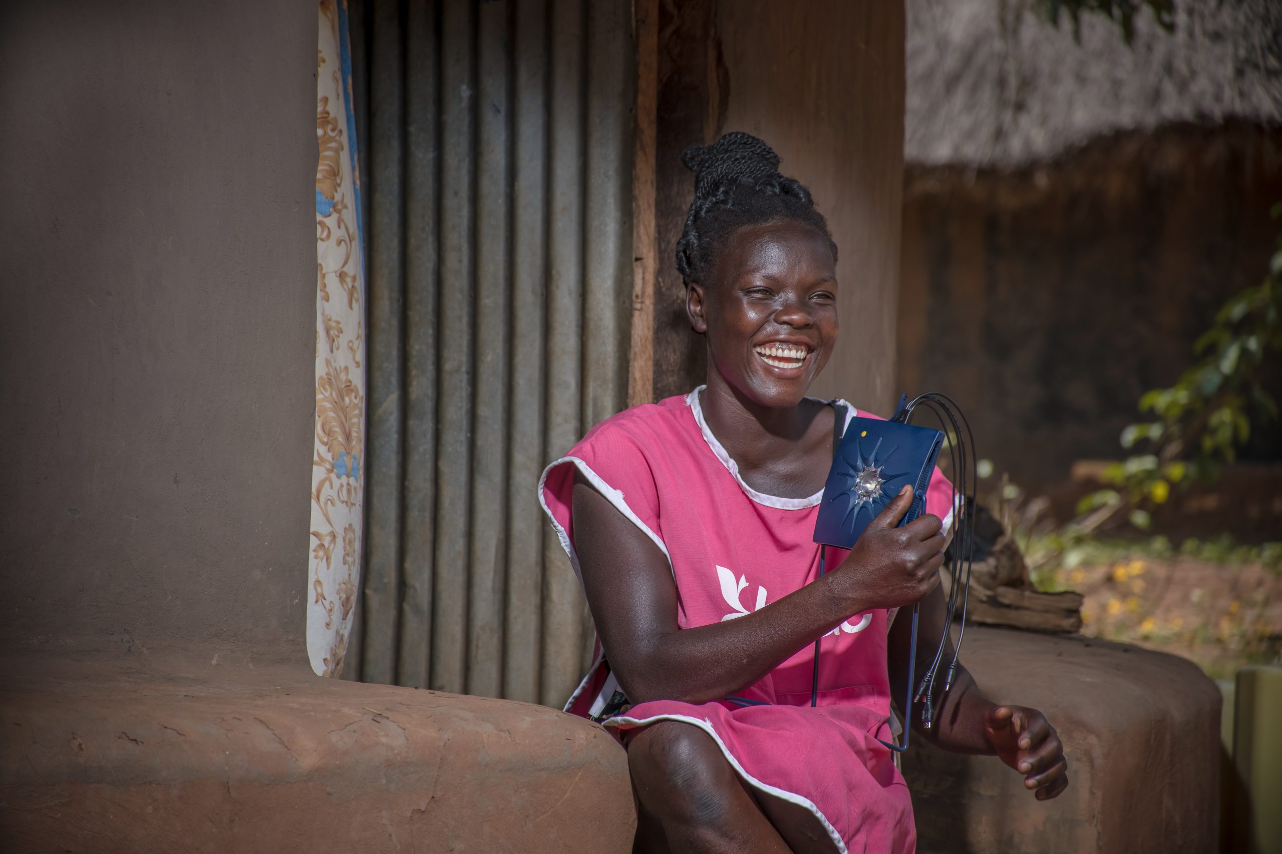 A girl with a Little Sun solar phone charger