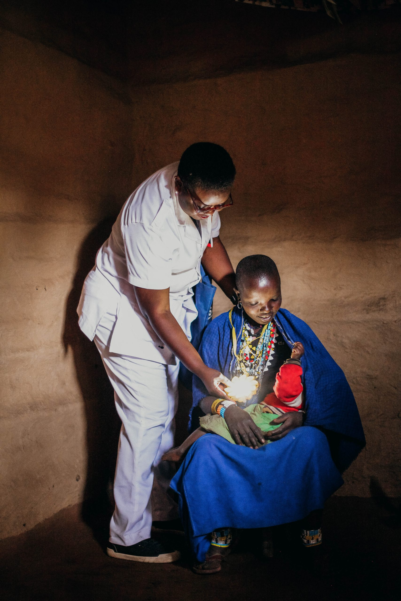 A young mother holding a healthy child and wearing a Little Sun solar lamp