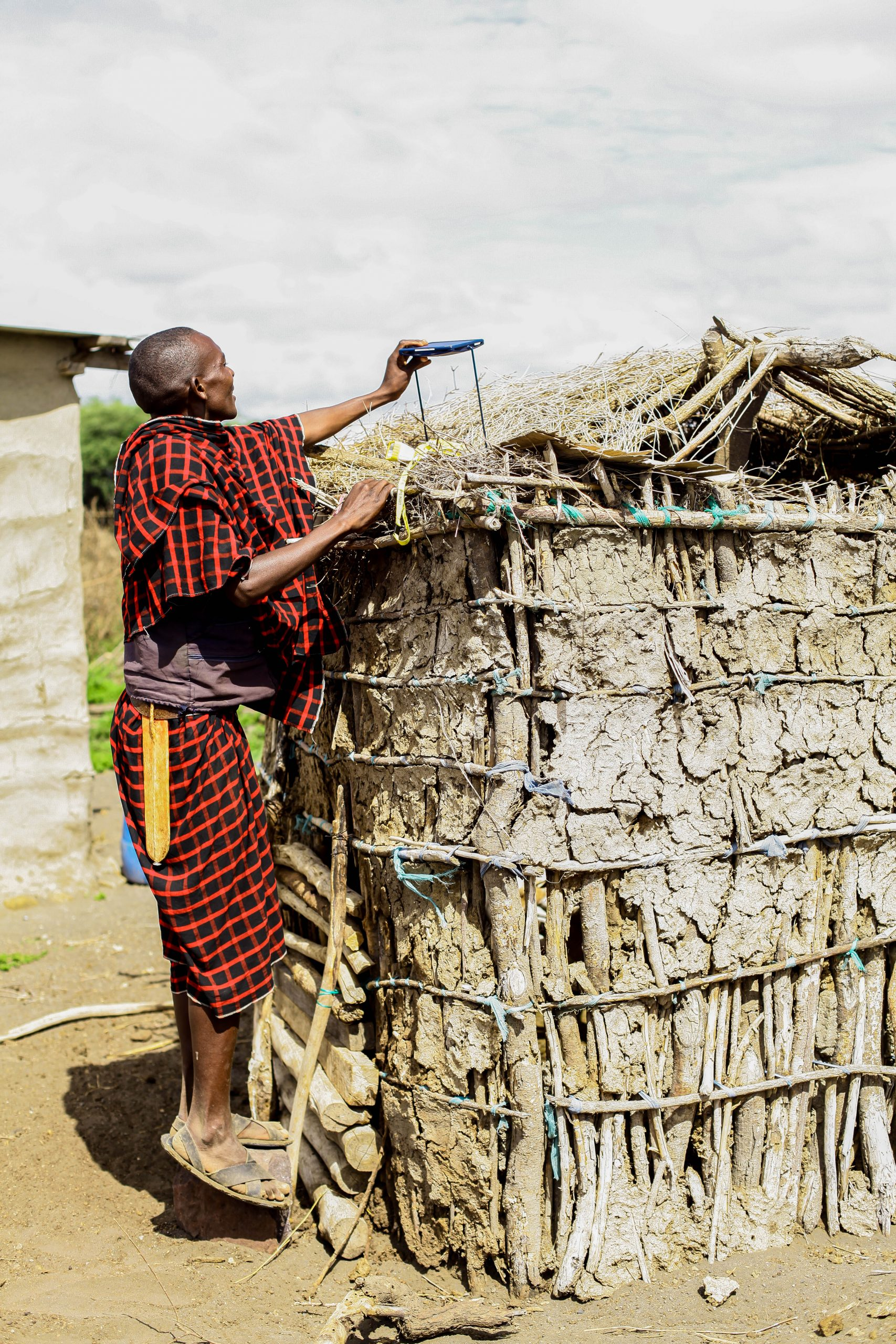 A woman in Tanzania charging her Little Sun solar charger to cook food for her family