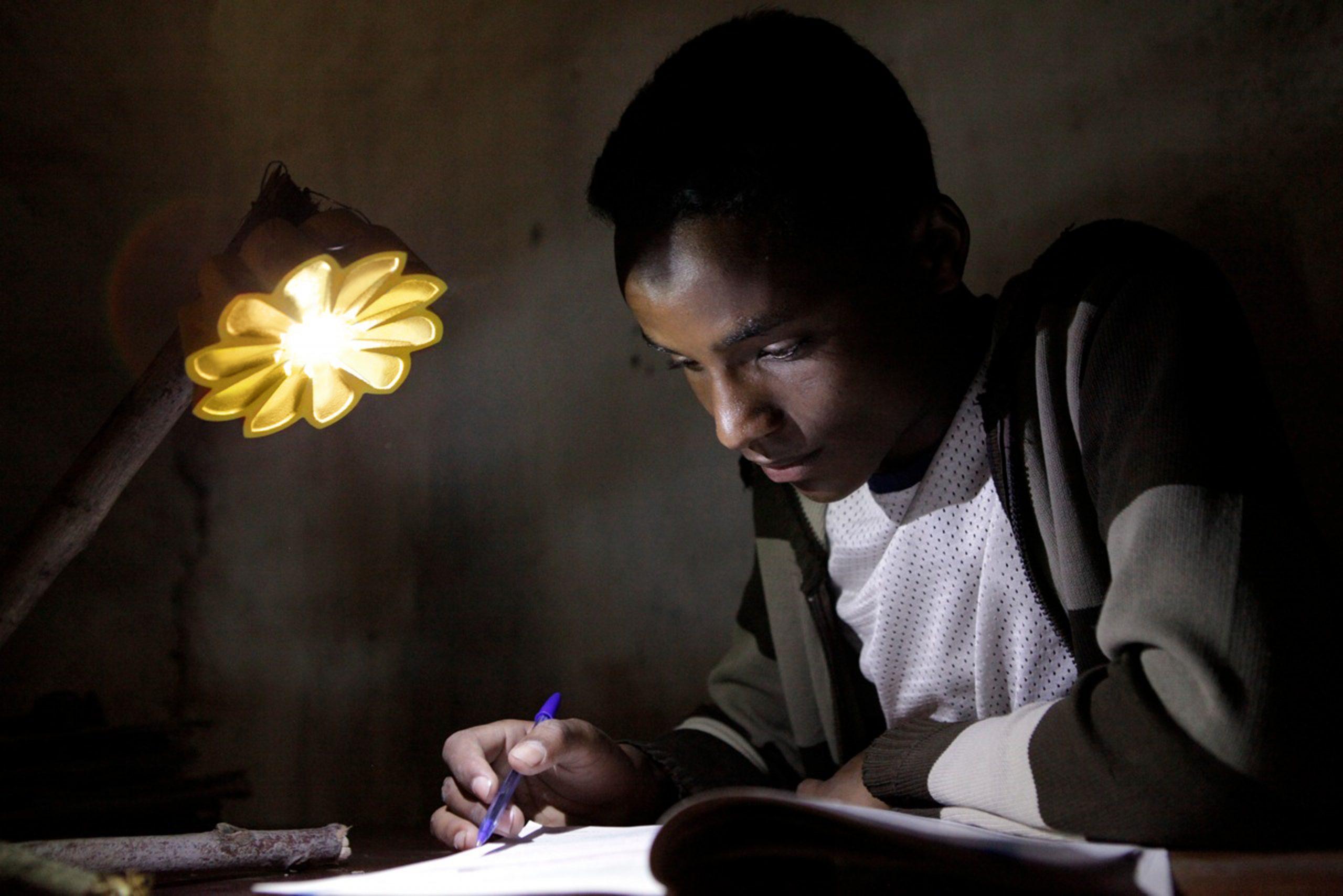 A school boy studying with a Little Sun solar lamp