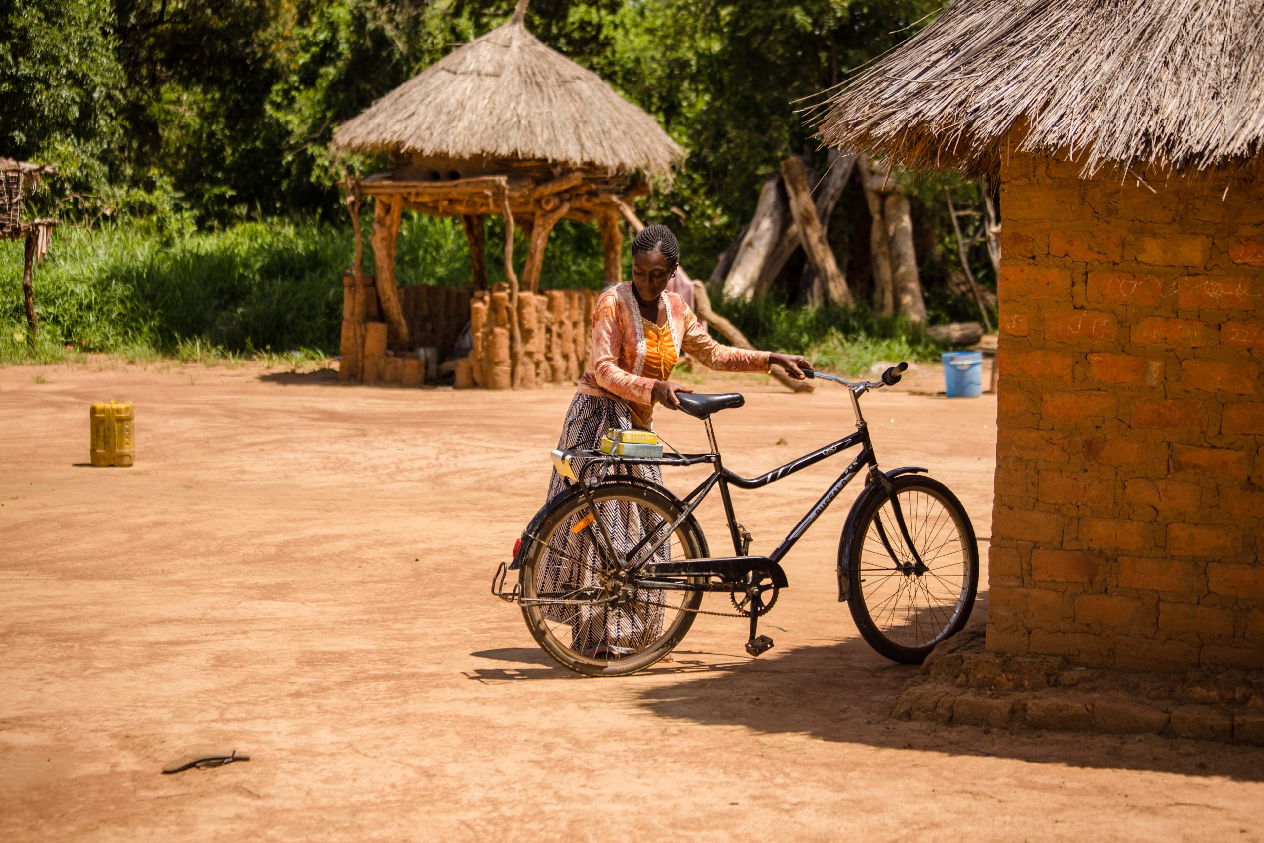 A woman with a bike distributing a Little Sun solar lamp for food security purposes