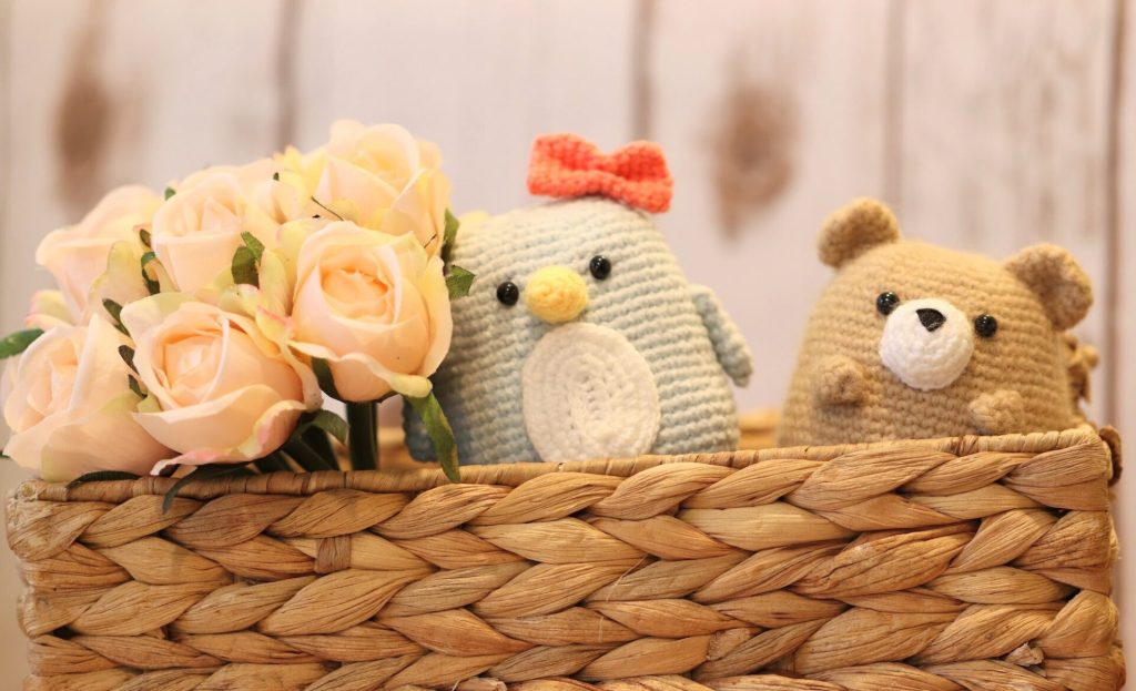amigurumi penguin and bear sitting next to each other in a basket with a bouquet of flowers next to them