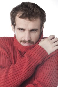 man shivering in red jumper
