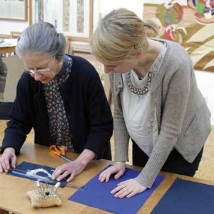 Two women stand at a ttable measuring fabric with a set of pins and other sewing tools around.