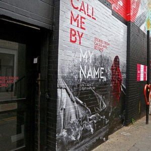 Exterior shot of the Call Me By My Name exhibit written on a brick wall outside the gallery