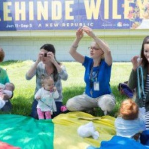 Several women sit in a circle with babies playing a hand game