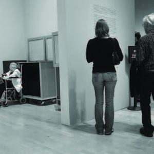 An older woman sits in a wheelchair in what looks like a coat room while two able bodied individuals stand reading wall text in a gallery around the corner