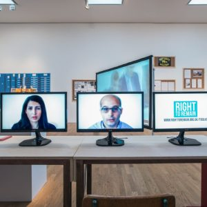 Image of a table with several screens showing people's faces