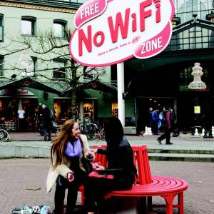 Two women sit on a round bench in front of a Free No WiFi Zone sign