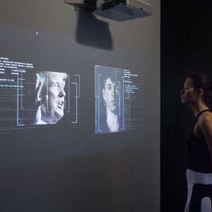 A woman stands looking at two images on a screen