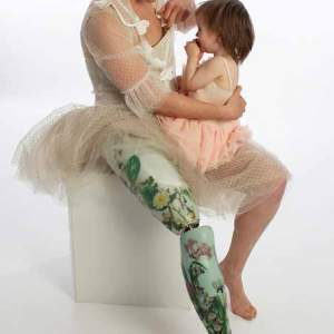 Image of a woman wearing a pink dress with a prostetic leg with a picture of flowers on it. She carries a child on her lap.