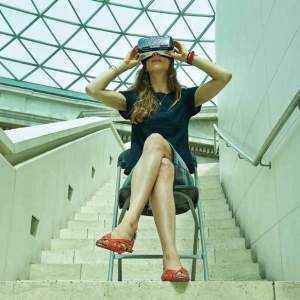 A woman sits on a metal folding chair on a staircase landing with a geometric patterned glass roof above wearing a pair of virtual reality glasses