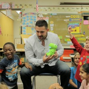 A man sits with a group of children holding a green dinosaur