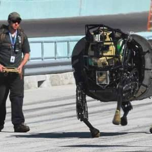 A man controls a large headless robot running down a road