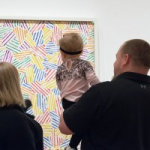 A couple holds a toddler while looking at a colorful artwork