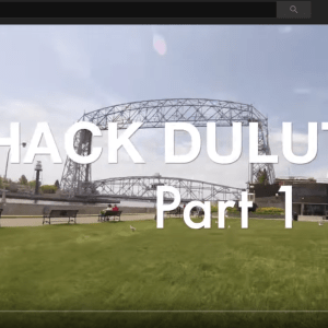 Image of a video screen with the words Hack Duluth Part 1 overlayed on top of an image of a bridge and park like area with people and dogs milling about.